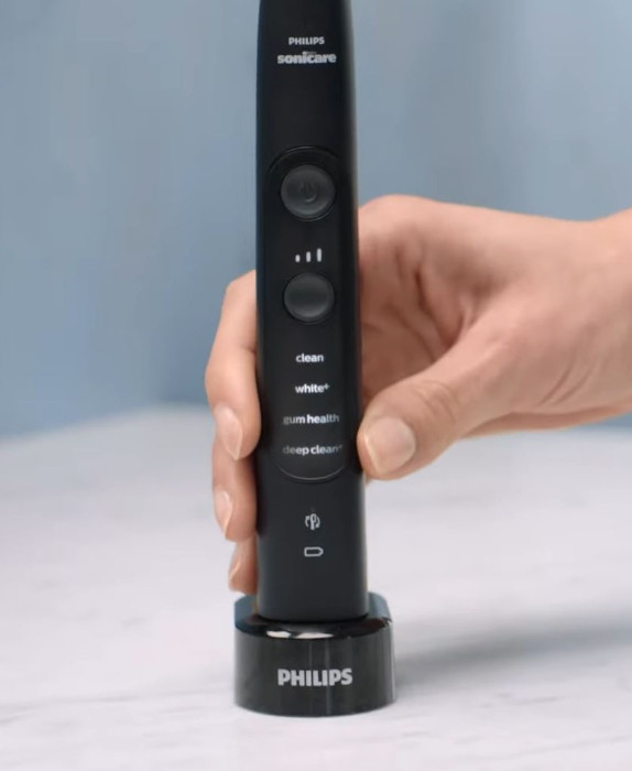 woman's hand putting Philips Sonicare ExpertClean 7500 on the charger