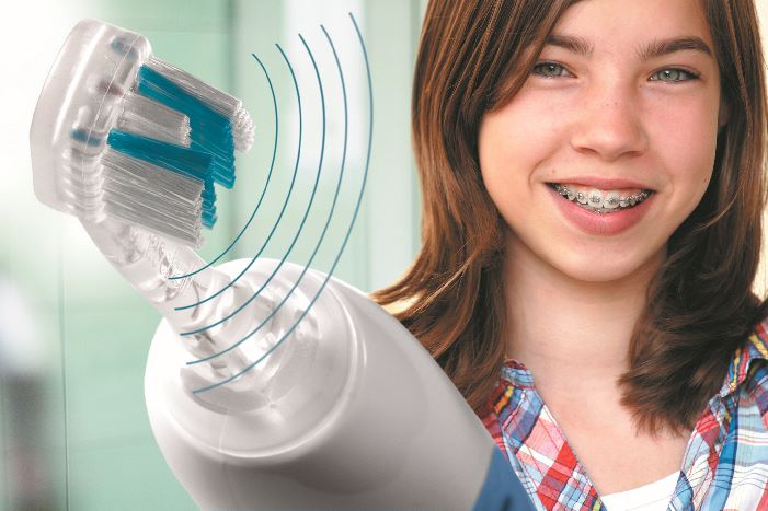 girl with braces holding Emmi-Dent Ultrasound toothbrush
