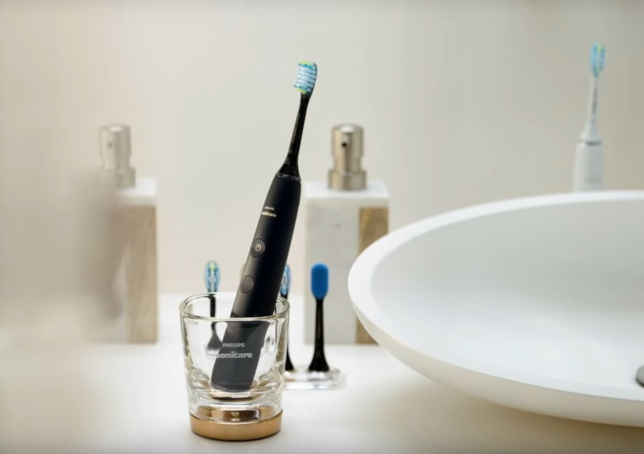 black philips sonicare diamondclean smart toothbrush in charging glass on bathroom counter
